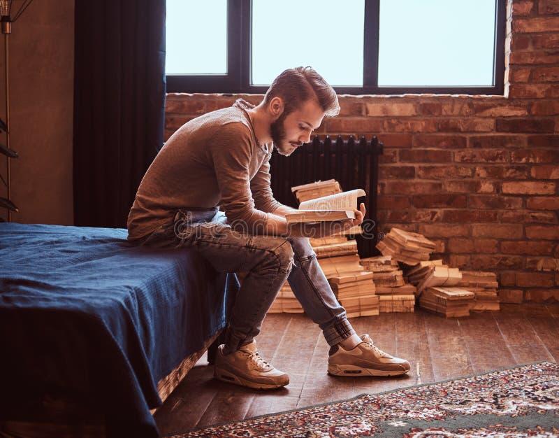 O estudante com barba e cabelo à moda está preparando-se para exames, está sentando-se na cama e está lendo-se um livro imagem de stock