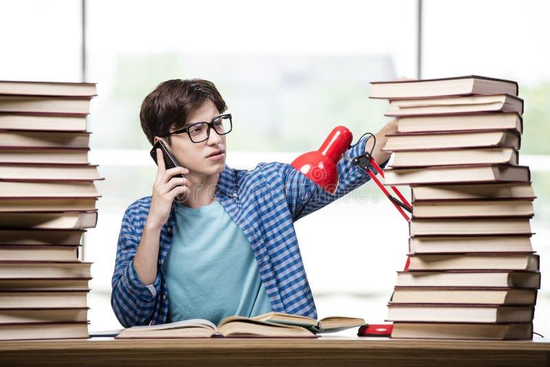 O estudante com lotes dos livros que preparam-se para exames foto de stock royalty free