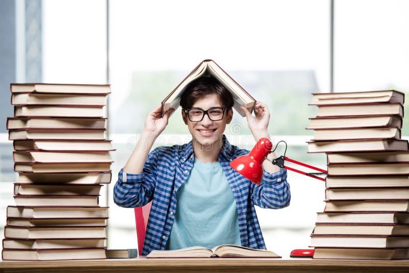 O estudante com lotes dos livros que preparam-se para exames imagem de stock