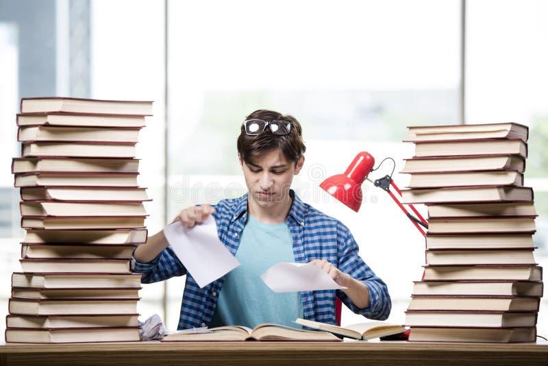 O estudante com lotes dos livros que preparam-se para exames imagens de stock royalty free