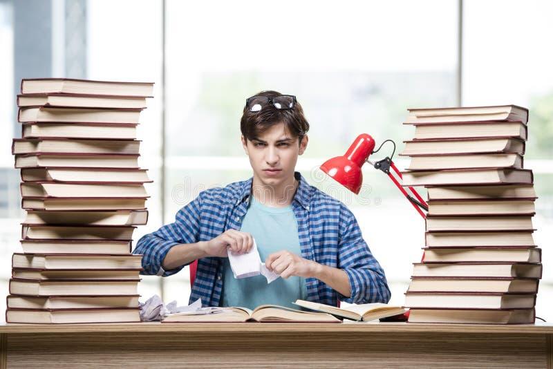 O estudante com lotes dos livros que preparam-se para exames fotografia de stock