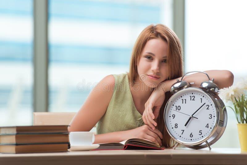 O estudante com o despertador de Gian que prepara-se para exames fotos de stock royalty free