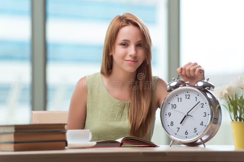 O estudante com o despertador de Gian que prepara-se para exames imagens de stock
