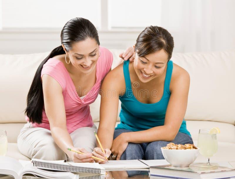 O estudante com os livros de texto que ajudam o amigo faz trabalhos de casa foto de stock royalty free