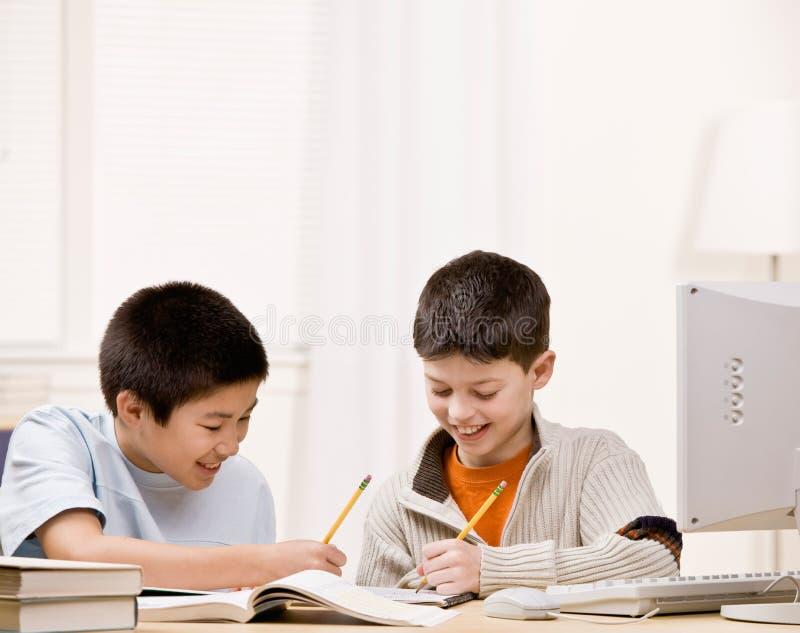 O estudante com os livros de texto que ajudam o amigo faz trabalhos de casa imagens de stock