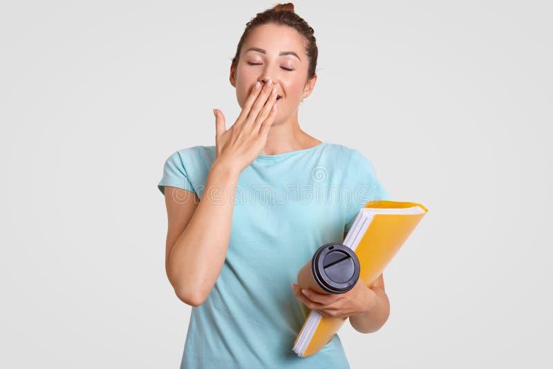 O estudante comely sobrecarregado cansado tem a expressão sonolento, boceja como as necessidades descansam, as tampas mouth com p fotografia de stock royalty free
