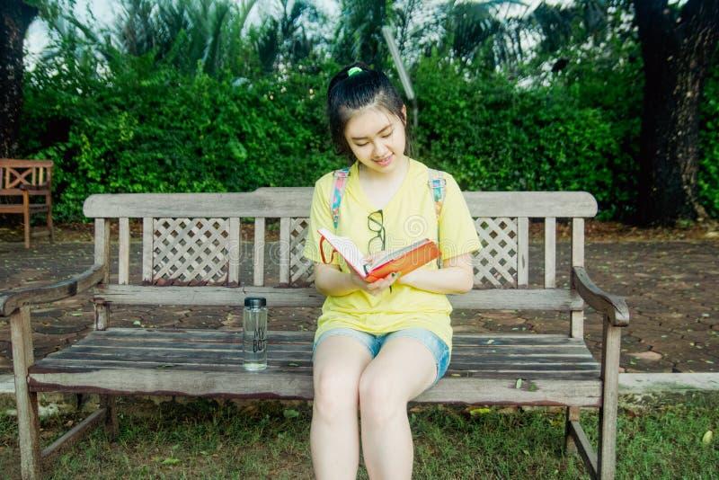 O estudante da moça lê um livro em um banco em um parque imagem de stock