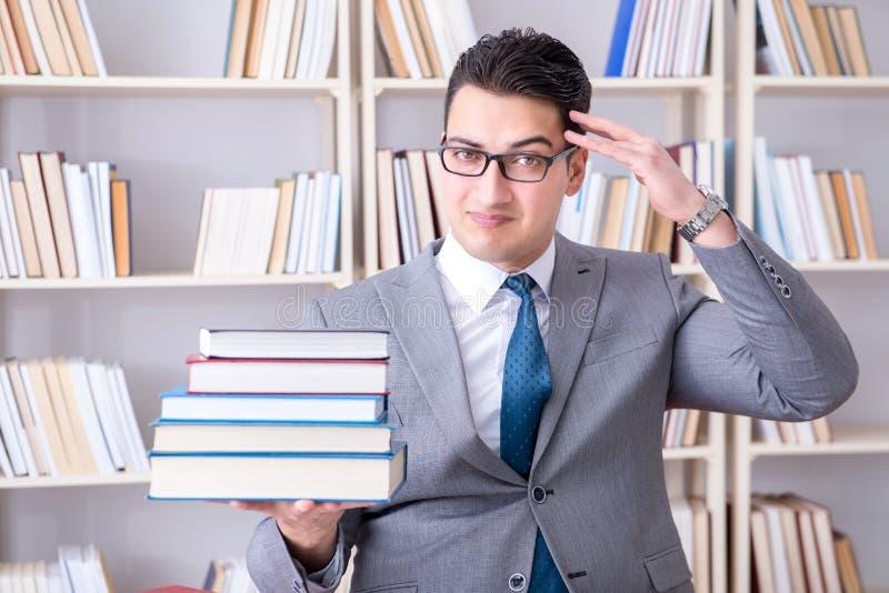 O estudante de direitos comerciais com a pilha dos livros que trabalham na biblioteca fotos de stock royalty free