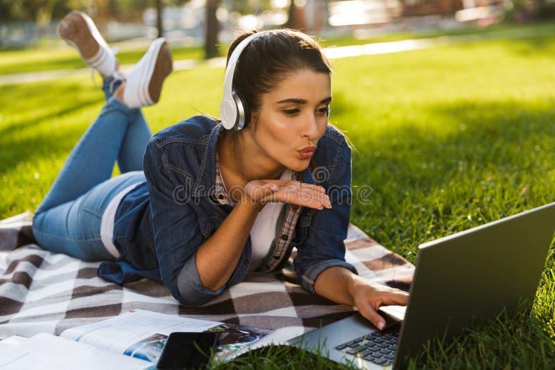 O estudante de mulher encontra-se fora em um parque usando beijos de sopro de escuta da música do laptop fotografia de stock royalty free