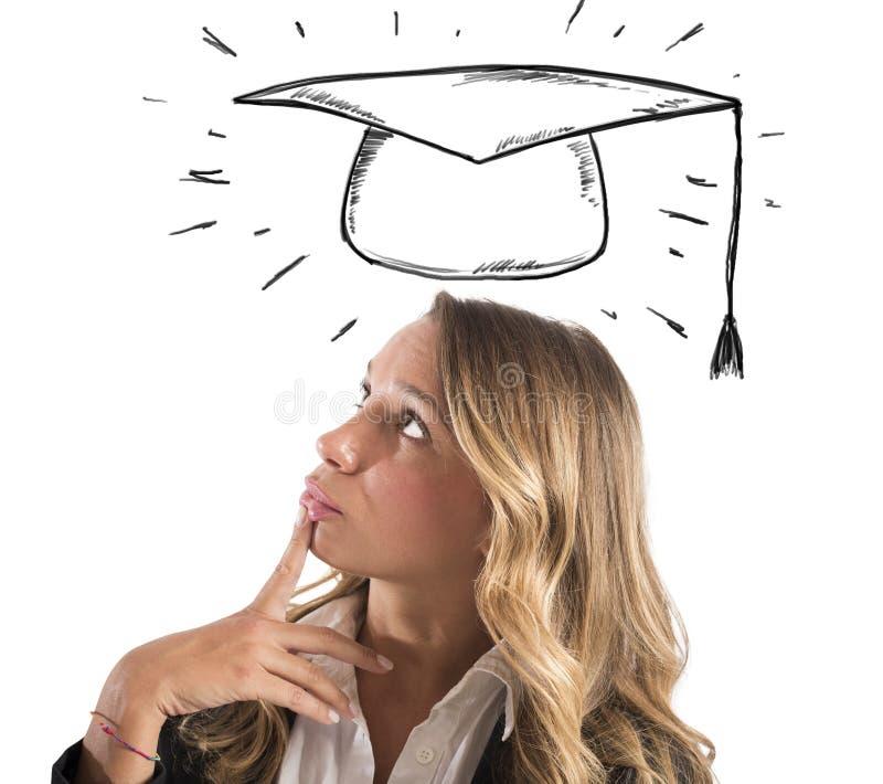 O estudante de mulher louro pensa sobre sua graduação fotografia de stock