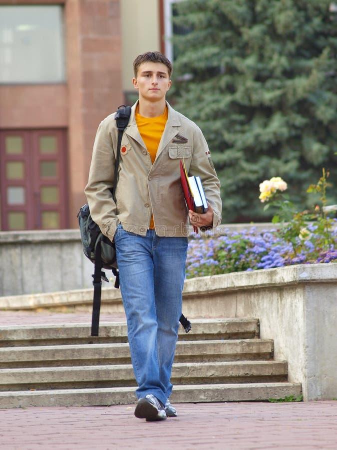 O estudante de passeio com os livros nas mãos foto de stock