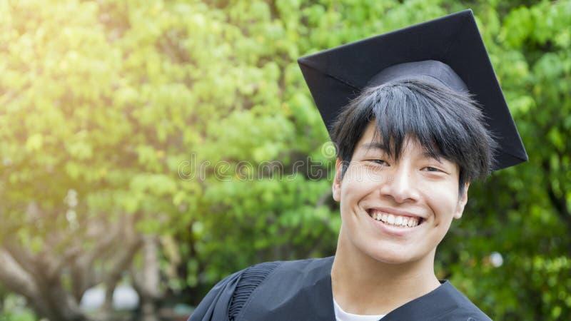 O estudante do homem sorri e sensação feliz em vestidos e em tampão da graduação fotos de stock