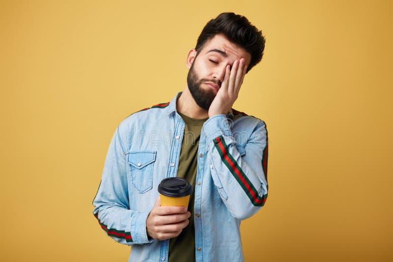 O estudante esgotado Tired com expressão sonolento, cobre a cara com a palma imagens de stock royalty free