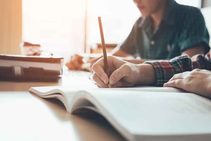 O estudante está estudando o papel e está escrevendo o teste na sala de aula moderna imagem de stock