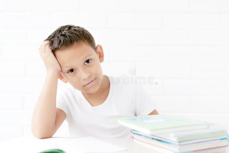 O estudante está sentando-se na tabela e aprende lições fotos de stock