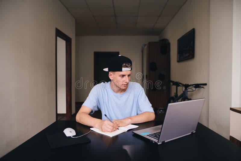 O estudante estuda em casa O adolescente olha o computador e escreve o texto ao caderno fotos de stock