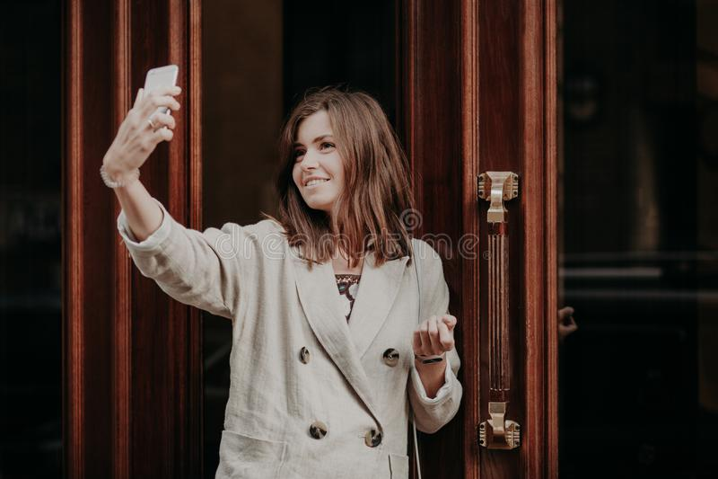 O estudante fêmea adorável levanta fazendo o selfie, usa o telefone celular moderno, vestido no revestimento branco, suportes per imagens de stock royalty free