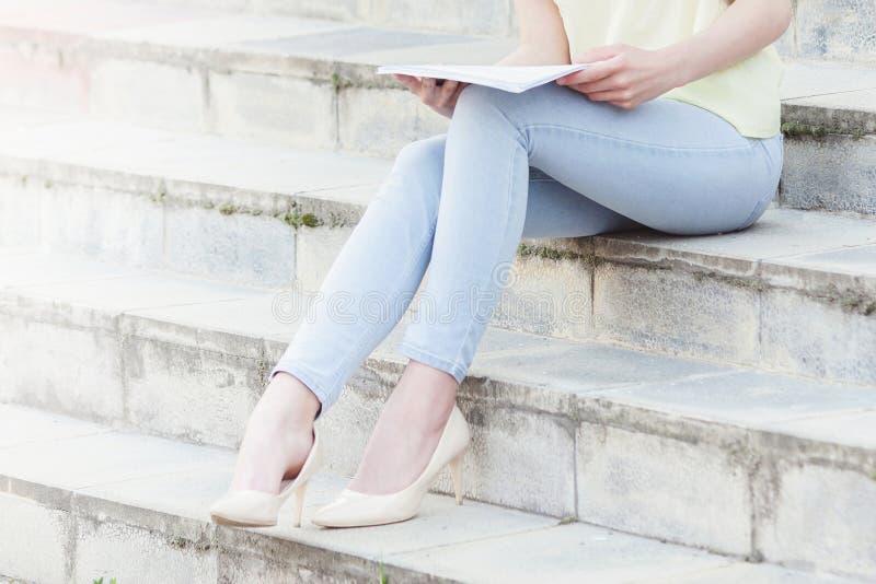 O estudante fêmea bonito novo está lendo em escadas imagem de stock royalty free