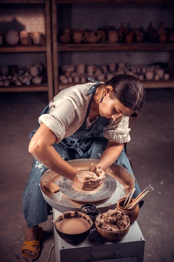 O estudante fêmea de encantamento do oleiro mostra como trabalhar com a roda da argila e da cerâmica Handwork imagens de stock