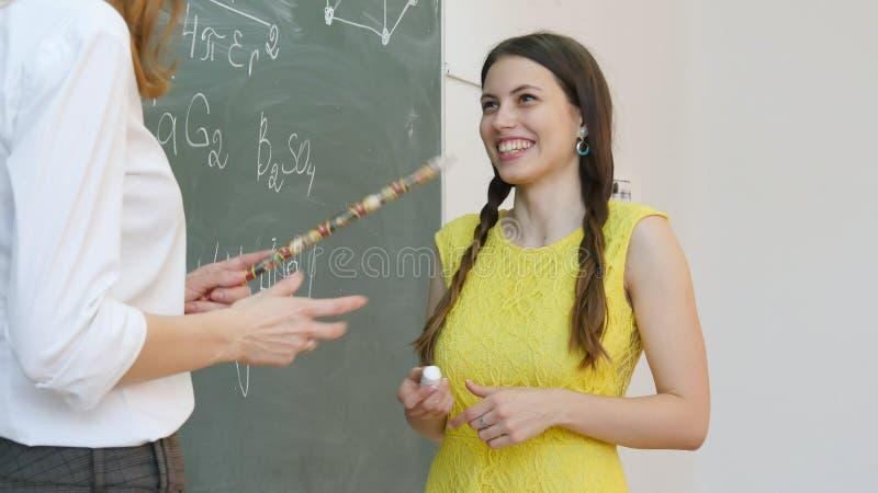 O estudante fêmea de sorriso que está na frente do quadro-negro e responde à pergunta fotos de stock royalty free