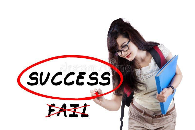O estudante fêmea escreve a palavra da motivação foto de stock