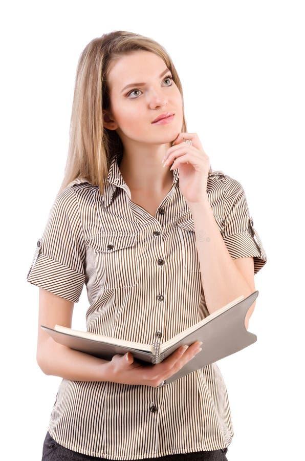 O estudante fêmea novo com as notas isoladas no branco imagens de stock