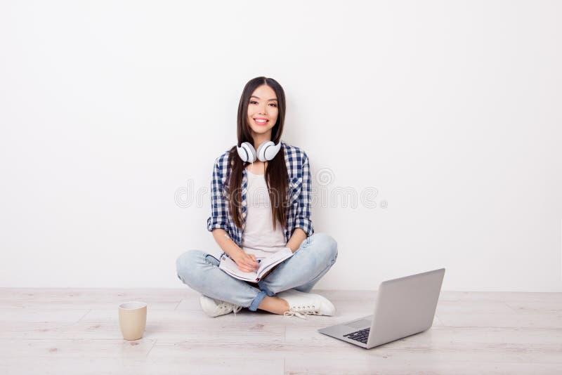 O estudante fêmea novo consideravelmente bonito está fazendo seus trabalhos de casa, listenin imagens de stock royalty free