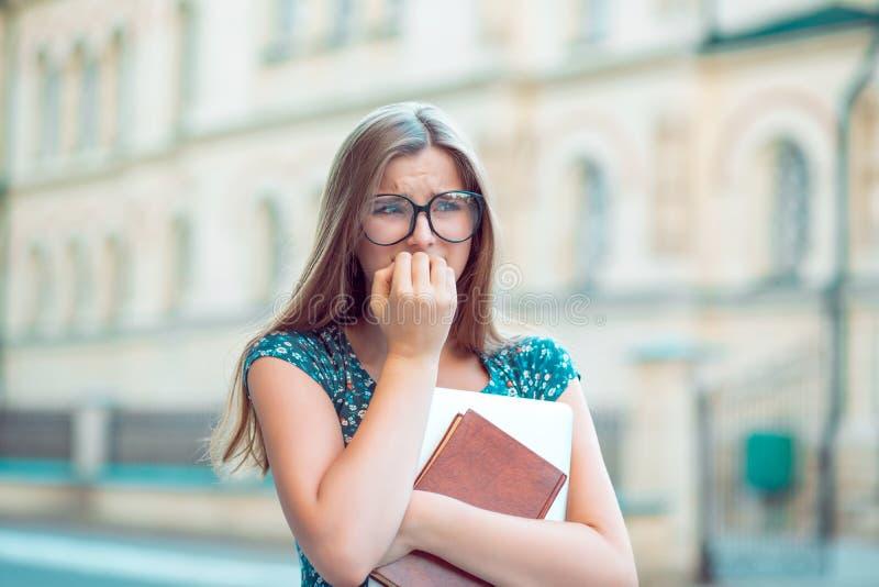 O estudante for?ou as unhas de mordedura da jovem mulher que olham afastado ansiosamente imagens de stock royalty free