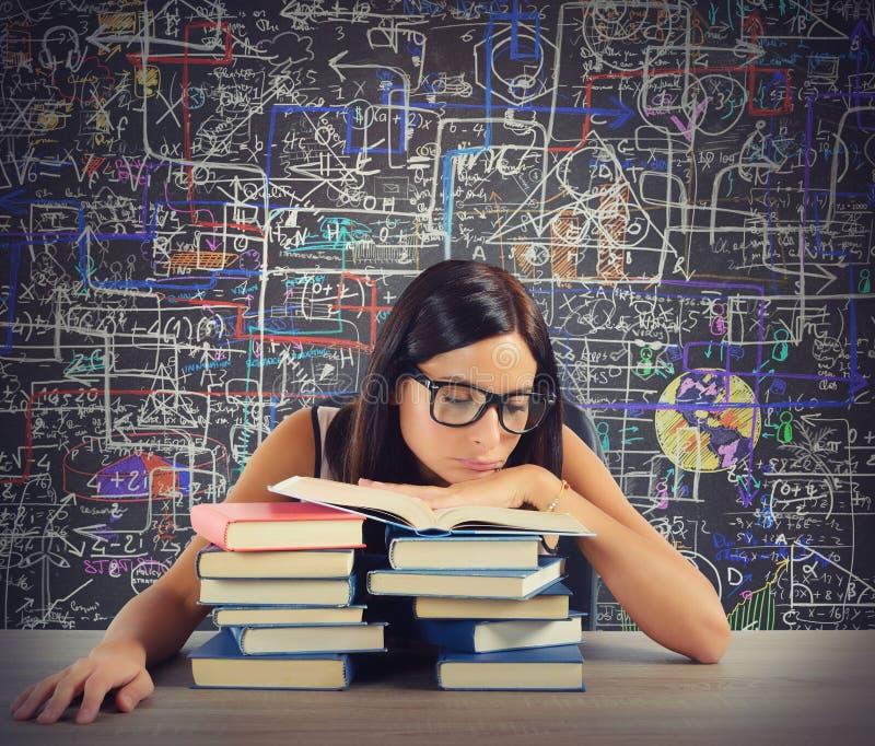 O estudante furado lê livros imagem de stock