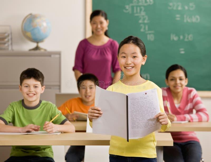 O estudante lê seu relatório na sala de aula da escola fotografia de stock royalty free