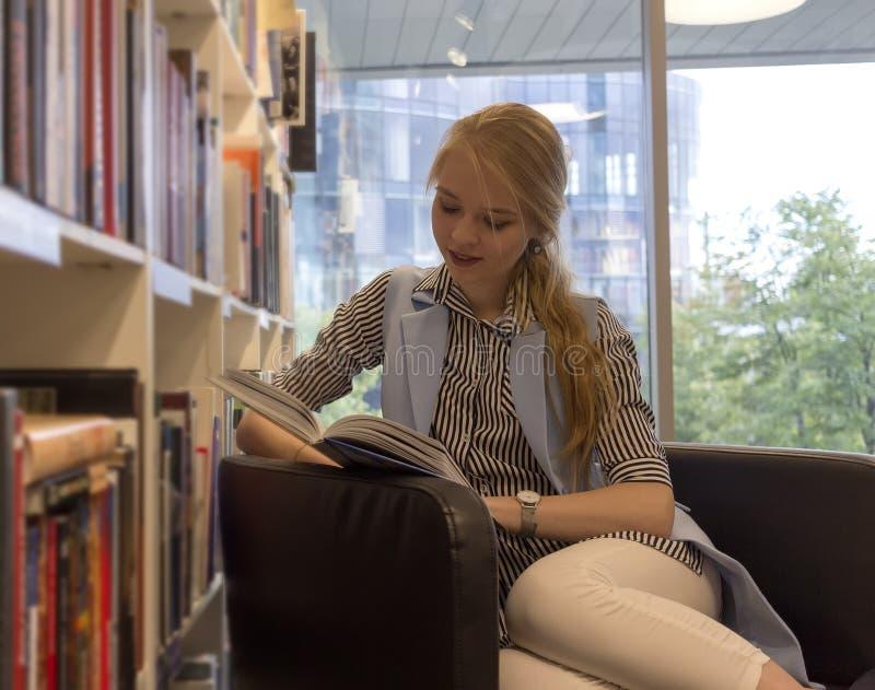 O estudante louro novo senta-se em uma cadeira e lê-se um livro na cremalheira com livros e janela no fundo fotografia de stock