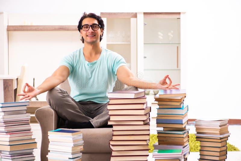 O estudante masculino com muitos livros em casa foto de stock royalty free
