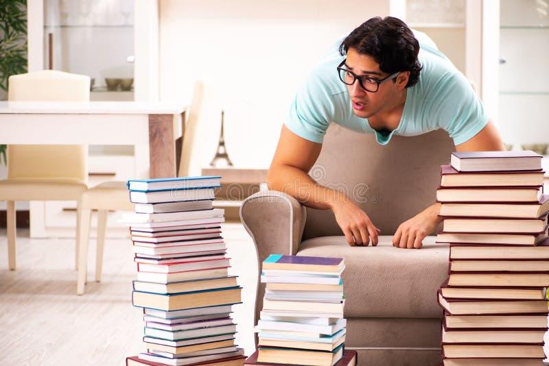 O estudante masculino com muitos livros em casa fotos de stock