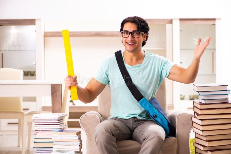 O estudante masculino com muitos livros em casa fotografia de stock royalty free