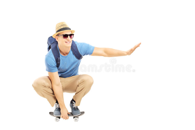 O estudante masculino de sorriso com trouxa que patina em um patim embarca fotos de stock