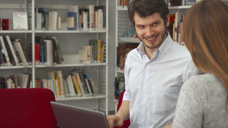 O estudante masculino mostra a seu colega fêmea algo no portátil na biblioteca imagem de stock royalty free