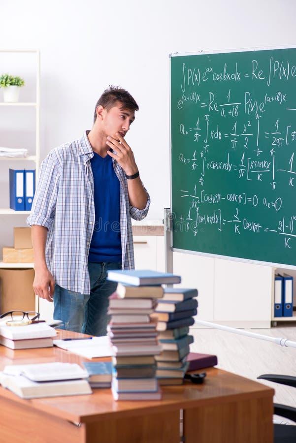 O estudante masculino novo que estuda a matemática na escola fotos de stock royalty free