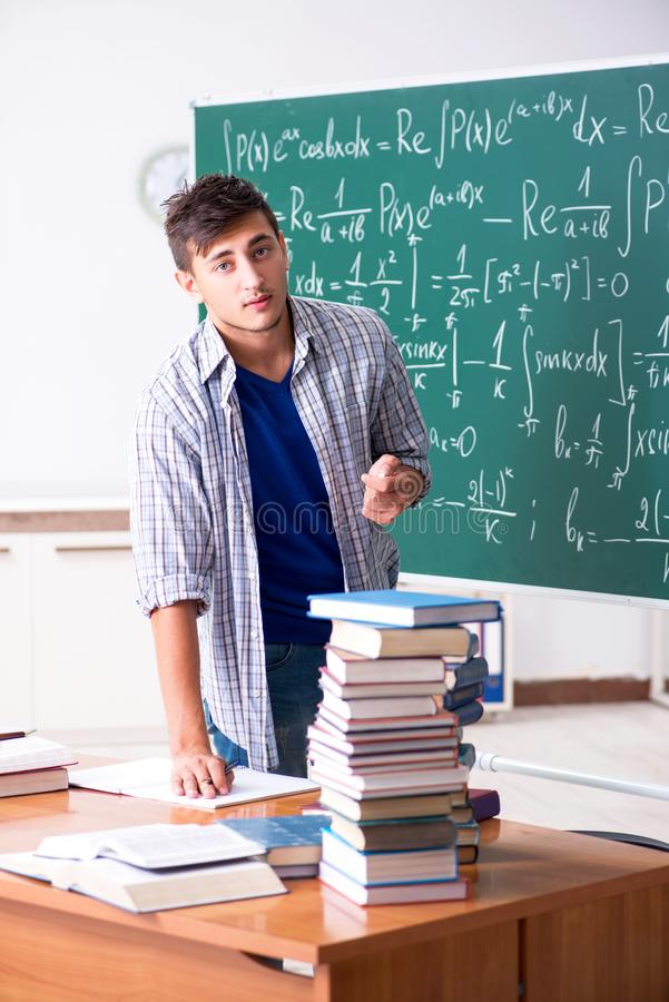 O estudante masculino novo que estuda a matemática na escola foto de stock royalty free