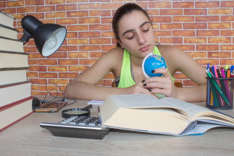 O estudante, menina escreve no caderno entre livros estudante atrativo novo Girl que estuda lições imagem de stock royalty free