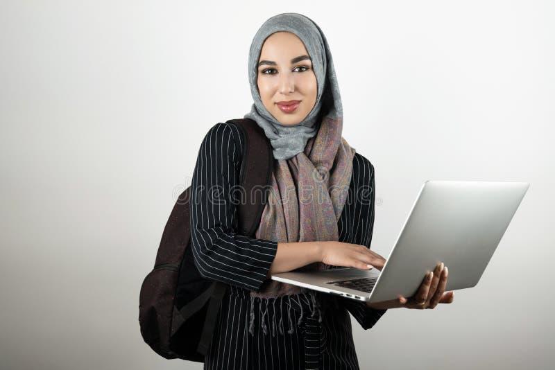 O estudante muçulmano atrativo novo com o bagpack que guarda e que bate seu lenço vestindo do hijab do turbante do portátil isolo imagem de stock royalty free