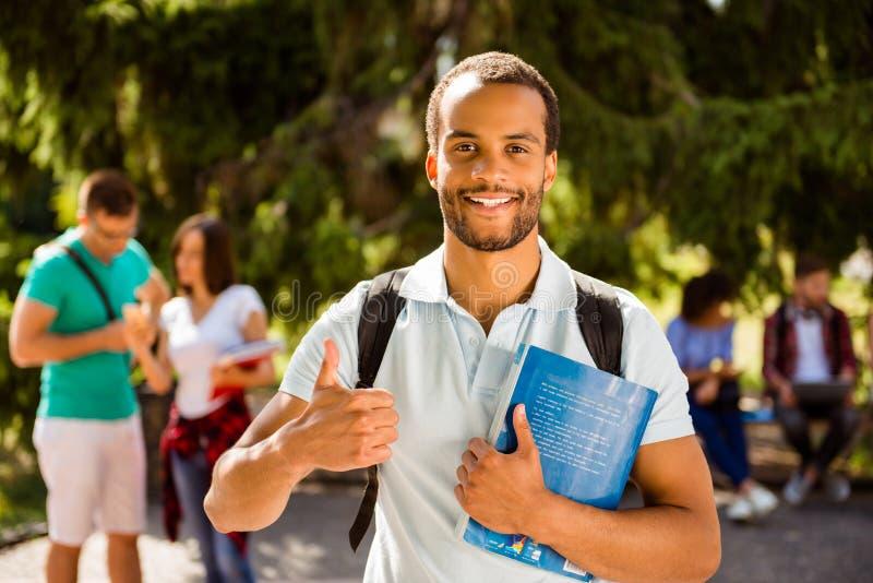 O estudante nerdy africano bem sucedido alegre novo está mostrando o polegar imagens de stock royalty free