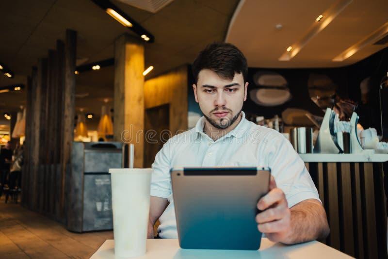 O estudante novo com um PC da tabuleta que senta-se em um restaurante agradável e toma a sua mão um o vidro da bebida de refresca foto de stock royalty free