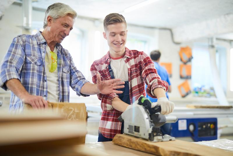 O estudante novo positivo da carpintaria que usa a circular viu na classe fotografia de stock
