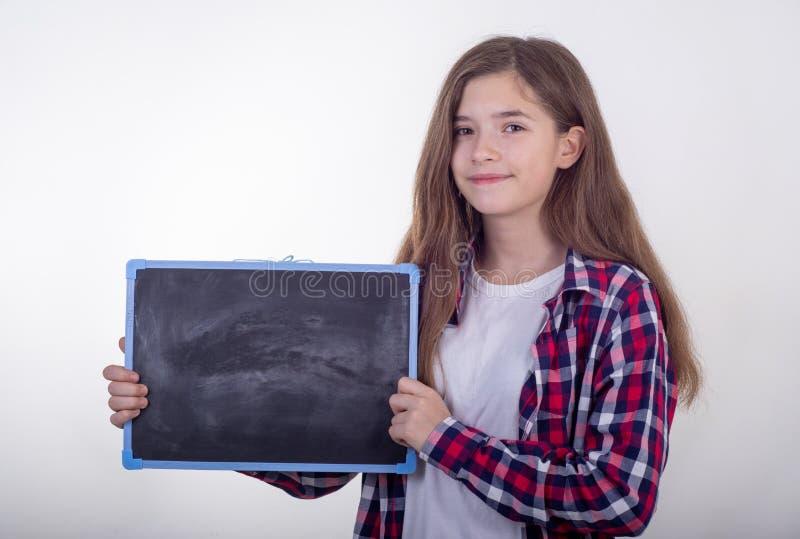 O estudante novo que guarda a placa preta com espaço vazio e anuncia algo fotos de stock