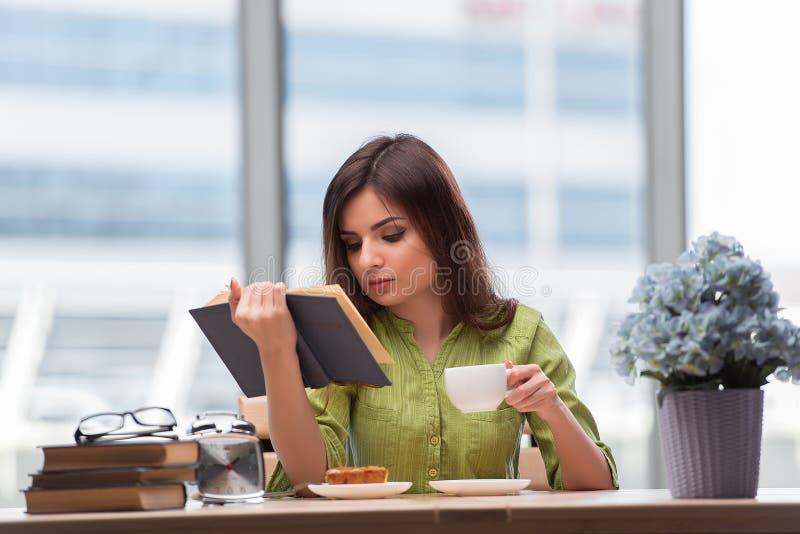 O estudante novo que prepara-se para os exames que bebem o chá foto de stock royalty free