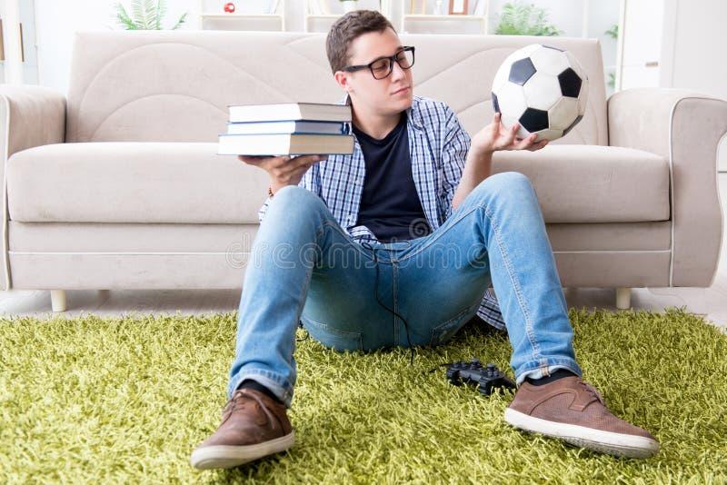 O estudante novo que tenta equilibrar o estudo e o jogo do futebol foto de stock