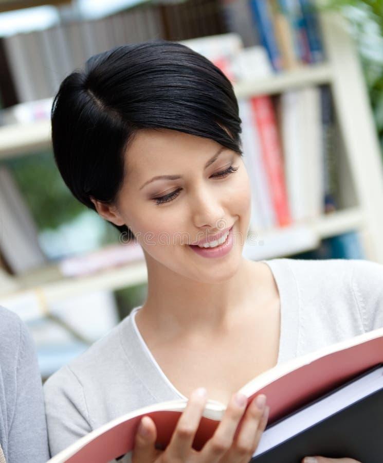 O estudante olha no livro na biblioteca fotografia de stock royalty free