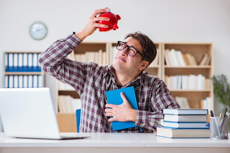 O estudante que quebra o piggybank para pagar por propinas imagem de stock