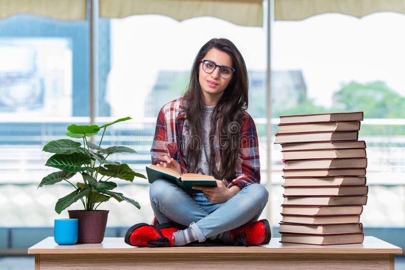 O estudante que senta-se na mesa com livros fotografia de stock royalty free