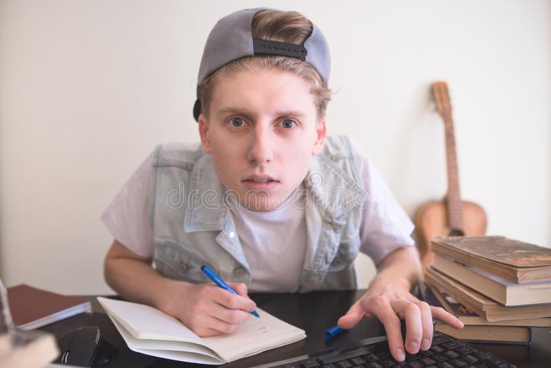 O estudante senta-se em um computador perto dos livros, olhares no monitor e escreve-se em um caderno imagem de stock